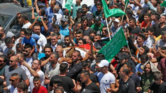 Mourners walk in a funeral procession with the body of human rights activist and critic of the Palestinian Authority Nizar Banat.