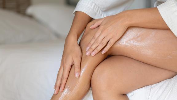 Woman applies cream on her legs