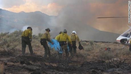 The Eldorado Hotshots medevac one of their own as Hump walks behind them during theNew York Peak Firein Nevada in 2006.