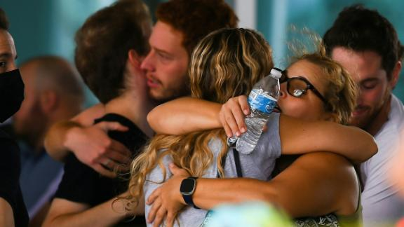 People hug June 25 as they wait for news about their relatives at a community center in Surfside.
