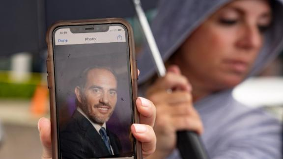 Toby Fried holds up a picture of her missing brother, Chaim Rosenberg, outside the Surfside Community Center on June 25.
