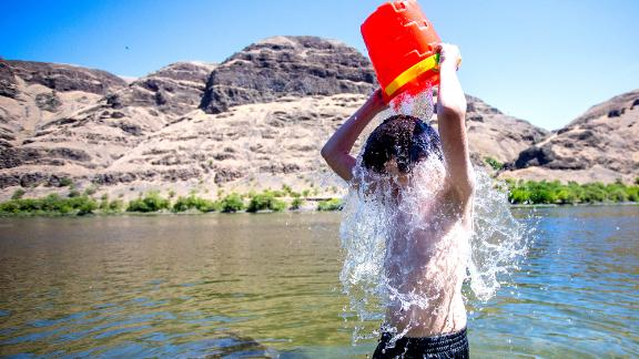 John Elizondo, 11, dumps a bucket of water over himself while playing in the Snake River at the edge of Asotin, Washington, on June 24.
