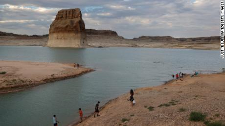 BIG WATER, UTAH - JUNE 23: Park visitors walk on an area of Lake Powell that used to be underwater at Lone Rock Beach on June 23, 2021 in Big Water, Utah. As severe drought grips parts of the Western United States, a below average flow of water is expected to flow through the Colorado River Basin into two of its biggest reservoirs, Lake Powell and Lake Mead. Lake Powell is currently at 34.56 percent of capacity, a historic low. The lake stands at 138.91 feet below full pool and has dropped 44 feet in the past year. The Colorado River Basin supplies water to 40 million people in seven western states. (Photo by Justin Sullivan/Getty Images)