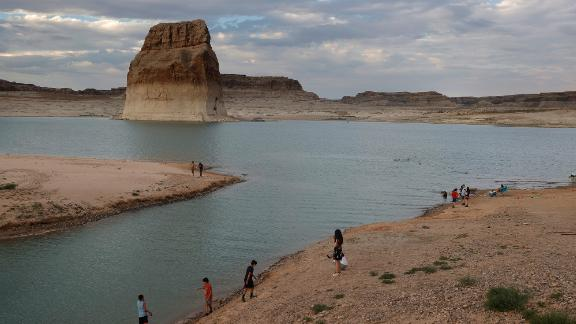 Park visitors in Big Water, Utah, walk on an area of Lake Powell that used to be underwater at Lone Rock Beach.