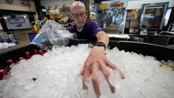 James Oehlerking spreads ice over a tub of bottled beer at Coors Field, the home of Major League Baseball's Colorado Rockies, on June 17. Temperatures were in the triple digits for a third straight day in Denver.