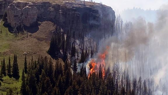 A wildfire burns on a canyon wall south of St. Xavier, Montana, on June 15. Record-high temperatures and gusting winds stoked a rapid expansion of major fires across central and eastern Montana.