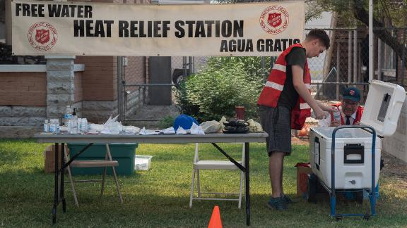 Adrian Keller, left, and Tim Smith fill a cooler with water at a Salvation Army heat-relief station in Phoenix on June 15.
