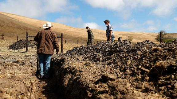 Ranchers Jim Jensen, center, and Bill Jensen inspect a trench they are working on to try to get more water to their ranch in Tomales, California, on June 8. As the drought continues in California, many ranchers and farmers are beginning to see their wells and ponds dry up. They are having to make modifications to their existing water resources or have water trucked in for their livestock.