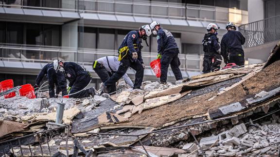 Members of a search-and-rescue team work in the rubble.