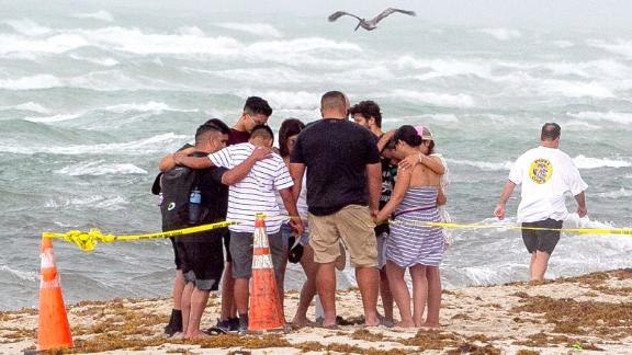 People pray together on the beach near the collapsed building.