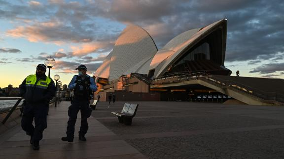 SYDNEY, AUSTRALIA - JUNE 26: Police officers walk past The Sydney Opera House during the first day of lockdown in Sydney, Australia, Saturday, June 26, 2021. The Australian state of New South Wales (NSW) on Friday announced COVID-19 lockdown in the capital Sydney after a new wave of COVID-19 outbreak in the city. (Photo by Steven Saphore/Anadolu Agency via Getty Images)