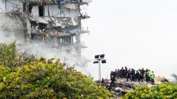 Rescue personnel search through the building's rubble on June 25.