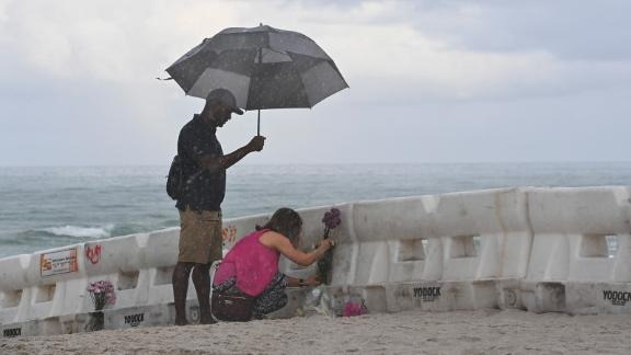 Eliagne Sanchez and K. Parker lay flowers on the beach near the partially collapsed building.