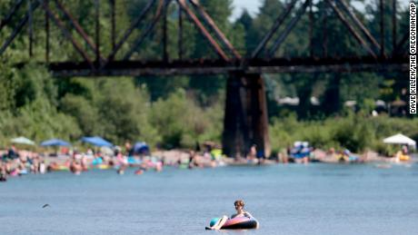 People gather at the Sandy River Delta in Oregon to cool off Friday.
