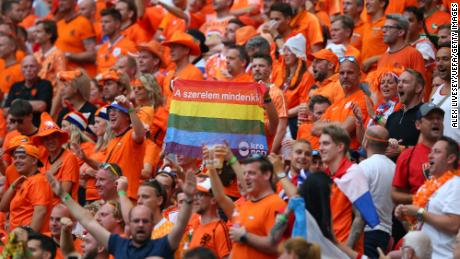 A fan of Netherlands is seen holding a rainbow flag.