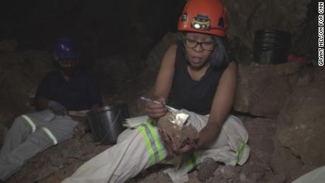 Molopyane sits in the UW 105 cave site examining a breccia block -- a rock made of different fragments -- for possible fossil remains.