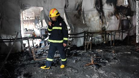 A firefighter investigates the fire scene at a martial arts school in China's Henan on June 25.