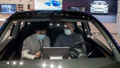 Two men sitting inside a Tesla Model 3 at a Tesla store in Beijing in May.