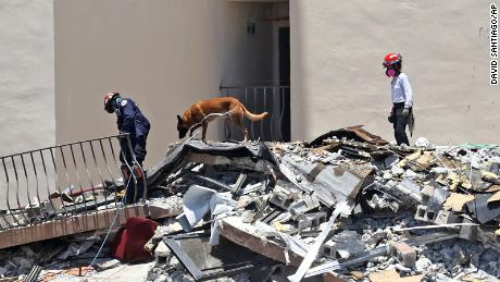 Search and rescue personnel search for survivors through the rubble with their dogs at the Champlain Towers South in Surfside, Fla., Sunday, June 27, 2021.