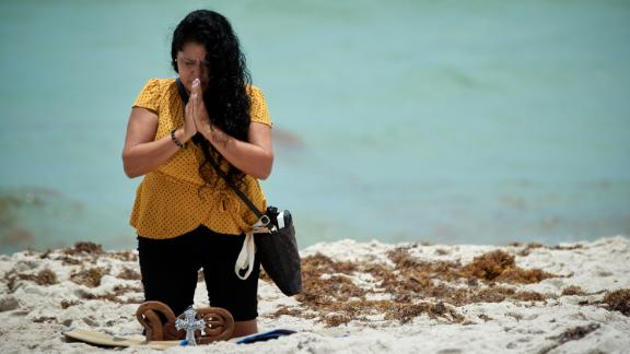 Luz Zenedith (originally from Columbia) prays for the victims on the eastern beach side of of the Champlain Towers South Condo building collapse - Surfside, Fl.  All Rights Reserved.  ©Jeffery Salter 2021 Please contact Photographer Jeffery Salter (305) 773 6356 or Jeff@Jefferysalter.com for additional usage.