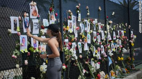Residents, friends and relatives visit the memorial wall of photos and flowers for the missing near the site of the collapse.