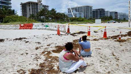 Beachgoers look at the site of the Champlain Towers South condo building collapse in Surfside, Florida.
