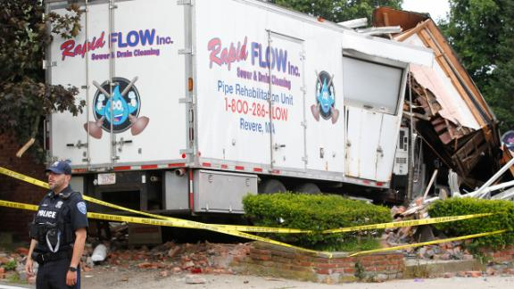 Police block the intersection where a truck collided with another vehicle and crashed into a building before a shooting.