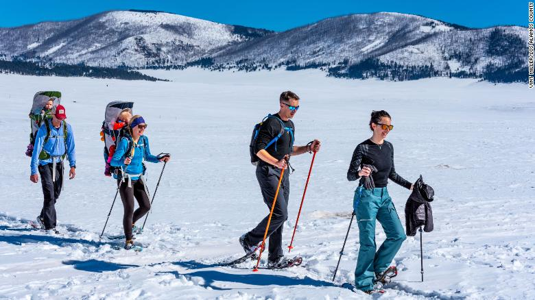 Families and individuals walk through a snow-covered valley in Los Alamos County, New Mexico.