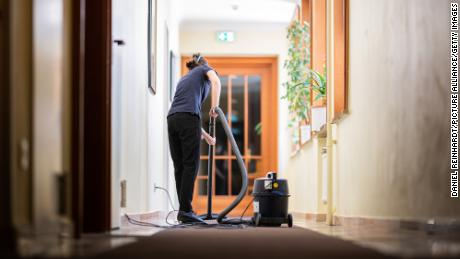 A woman vacuums a hallway in a hotel on May 31, 2021, in Hamburg. Since June 1, hotels in Hamburg have been allowed to receive guests again at 60% capacity.
