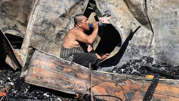 Carlos Torres drinks water on Saturday as he looks for paperwork in his destroyed mobile home in Kelseyville, California. A wind-whipped brush fire burned three mobile homes, two separate garages and vehicles, a single-family dwelling and outbuildings.