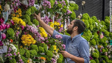 Leo Souto adds flowers to a memorial featuring photos of some of those lost in the partially collapsed Champlain Towers South building.