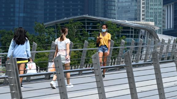 People walk along a pedestrian bridge at the financial business district in Singapore on June 25, 2021. (Photo by Roslan RAHMAN / AFP) (Photo by ROSLAN RAHMAN/AFP via Getty Images)