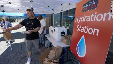 Carlos Ramos hands out bottles of water and sack luncheson Monday at a hydration station in front of the Union Gospel Mission in Seattle.