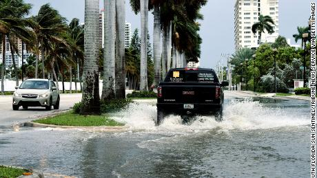 Cars maneuver through high-tide flooding in Fort Lauderdale, Florida.