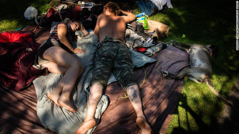 A couple and their dog lie in the shade Monday in Portland, Oregon. Portland had another record-high temperature on Monday: 116 degrees.