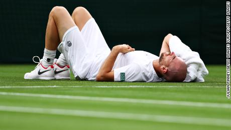 Adrian Mannarino of France reacts as he goes down with an injury in his first-round match against Roger Federer.