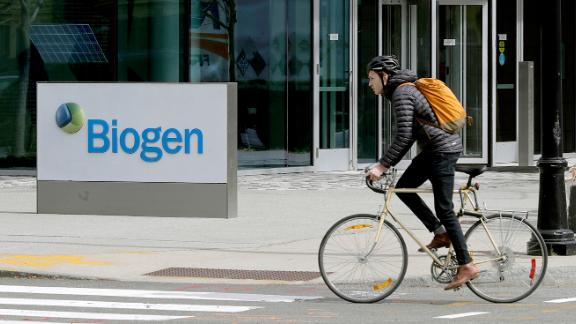 People pass the Biogen Inc., headquarters, Wednesday, March 11, 2020, in Cambridge, Mass. (AP Photo/Steven Senne)