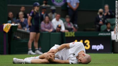 Mannarino memegang lututnya setelah tergelincir di depan Federer.