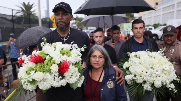 NBA basketball player Udonis Haslem, left, and Miami-Dade County Mayor Daniella Levine Cava arrive to pay their respects at a memorial near the building on June 30.