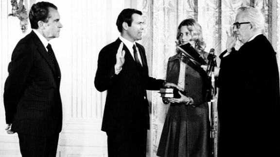 Donald Rumsfeld, second from right, new United Nations ambassador to the North Atlantic Treaty Organization, takes oath of office from Chief Justice Warren E. Burger, right, during a ceremony on February 2,1973, at the White House. President Richard M. Nixon looks on at left and Mrs. Joyce Rumsfeld holds a Bible  for her husband.
