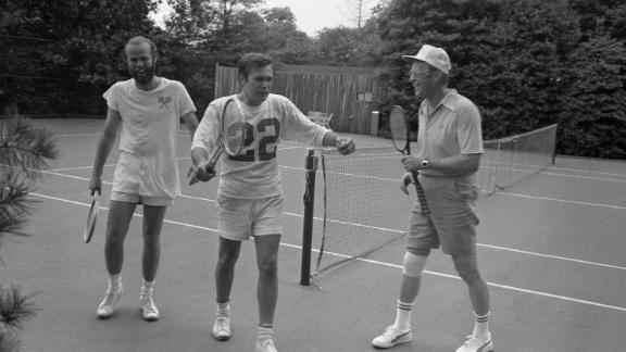 Rumsfeld, center, plays tennis at the White House with President Ford, right, and chief White House photographer David Hume Kennerly in 1975.