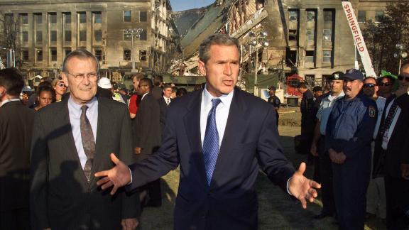 Rumsfeld, left, joins Bush as they visit the Pentagon following the terrorist attacks on September 11, 2001.