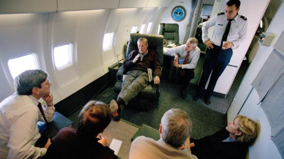 Rumsfeld talks to staff members aboard a plane en route to Saudi Arabia in October 2001.