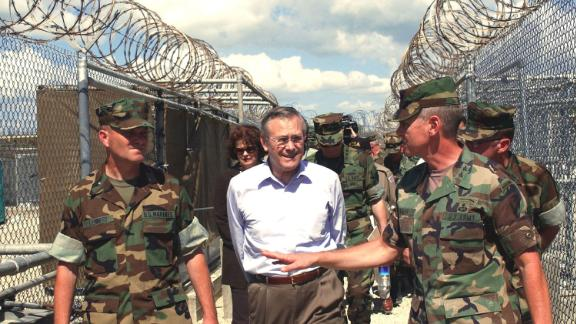 Rumsfeld tours the detention facility Camp X-Ray while visiting Guantanamo Bay, Cuba, in 2002. Rumsfeld said that the Taliban and al Qaeda prisoners being held at the base would not be given prisoner-of-war status.