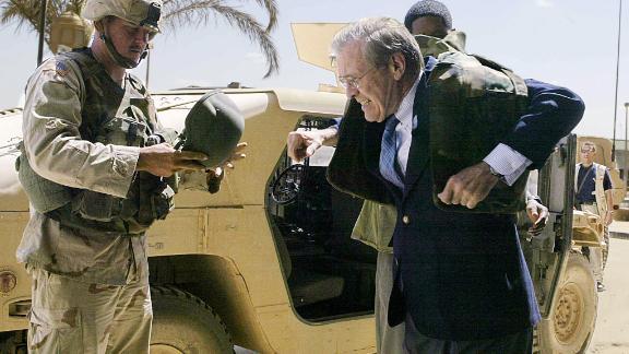 Rumsfeld puts on a bulletproof jacket while visiting Baghdad, Iraq, in April 2003.