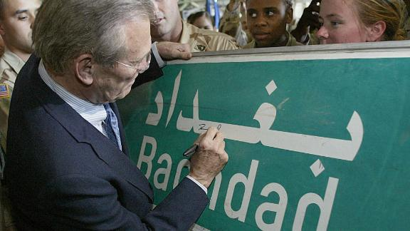 Rumsfeld signs a Baghdad road sign at the request of a US soldier in April 2003.