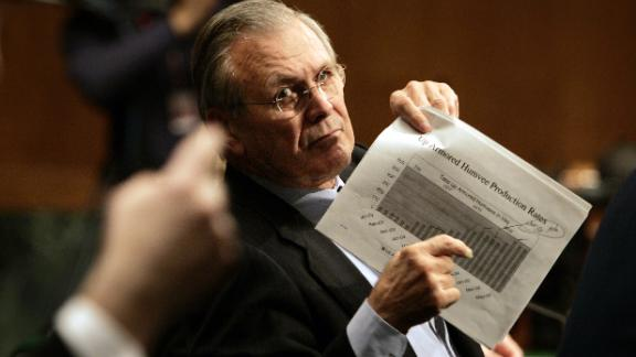 Rumsfeld motions to an aide to display a chart detailing production of armored Humvees as he is questioned during his testimony to the Senate Appropriations Committee in February 2005.