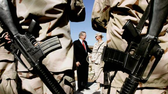 US soldiers from the 173rd Airborne Brigade wait to have their picture taken with Rumsfeld in Kandahar, Afghanistan, in December 2005.