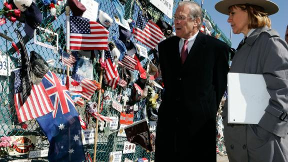 Rumsfeld is escorted by Joanna Hanley, superintendent of the Flight 93 Memorial, as he looks at tributes in Shanksville, Pennsylvania, in March 2006.
