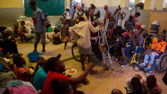 A group of blind and disabled people eat at a refuge for displaced persons after armed gangs set their homes on fire in Port au Prince, Haiti, Thursday, June 24, 2021. (AP Photo/Joseph Odelyn)